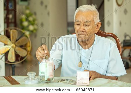 senior man counting money with glass bank