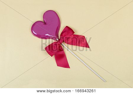 Light violet heart shaped lollipop with red sateen bow on light yellow background with slight shimmer.