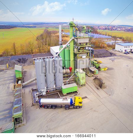 Aerial view to tarmacadam plant near new highway construction. Air pollution and climate change theme. Transportation industry and environment.