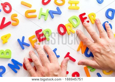 Lots Of Colorful Letters On A Table, Hands Forming Text, Keep Order