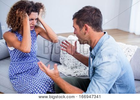 Young couple sitting together and discussing after a fight at home