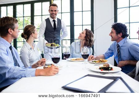 Waiter serving salad to the business people in restaurant