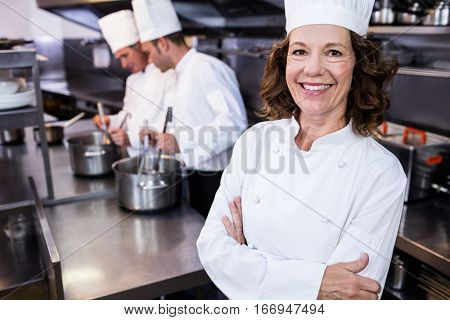 Portrait of smiling chef in commercial kitchen and thee chefs cooking in background