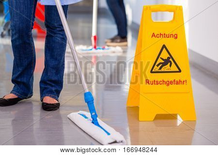 Warning sign in front of cleaning crew, the floor is wet and there is danger of accidents