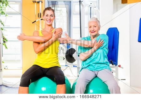 Senior and young woman on fitness ball doing stretching or gymnastics in gym