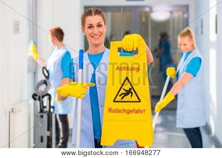 Cleaning lady showing warning sign because the floor is wet and there is danger of accidents