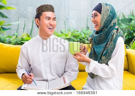 Asian Muslim man and woman drinking coffee or tea in living room wearing traditional dress