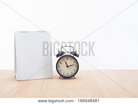 blank calendar planner with clock and wood desk office on white background.
