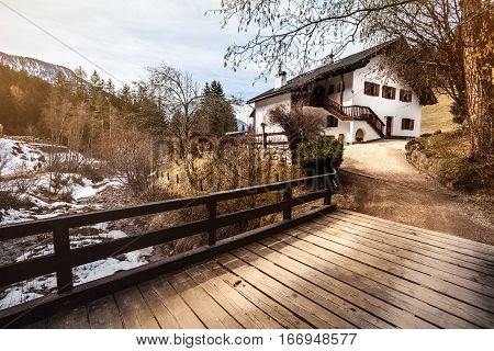 House in the mountains, snow and wooden bridge. A rustic mountain home. A bridge with wooden planks, river with snow, mountains and forest. Location: Ortisei, Northern Italy.