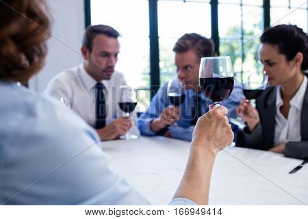 Group of businesspeople drinking wine glass during business lunch meeting in a restaurant