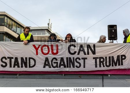 People put up anti Donald Trump banner. Stockholm, Sweden - January 21, 2017: Anti Donald Trump banner and people at demonstration in Stockholm January 21, 2017. People behind anti Donald Trump banner.