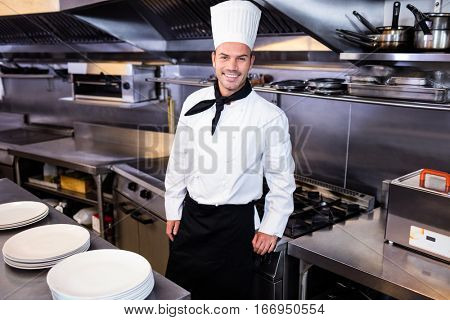 Portrait of happy male chef standing in kitchen