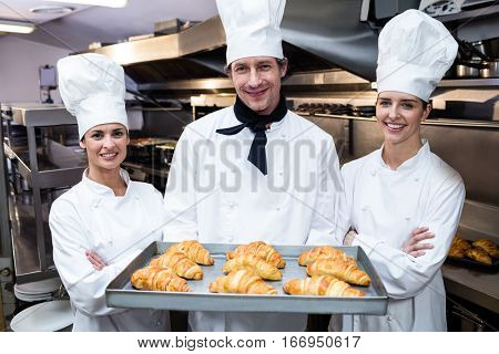Three chefs in kitchen holding a tray of baked croissant in commercial kitchen