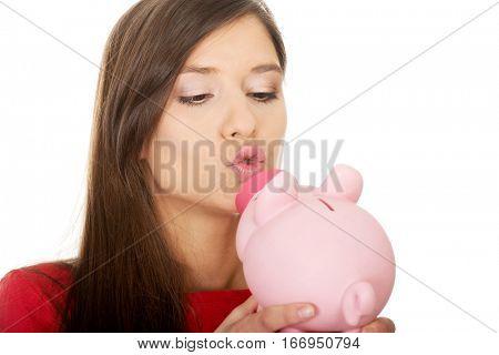Young woman kissing a piggybank.
