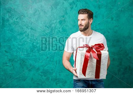 Handsome man in the white t-shirt holding gift box on the painted green wall background. Valentine's Day concept