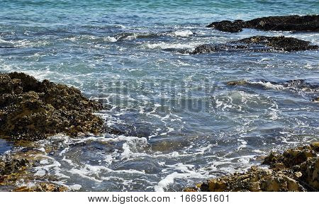 beautiful gentle Waves gently flowing over rocks on the out going tide early in the morning