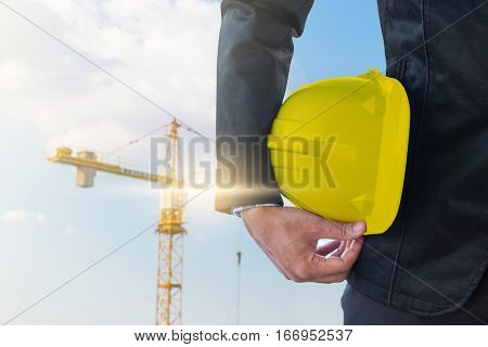 The business man holding the yellow safety helmet with crane background