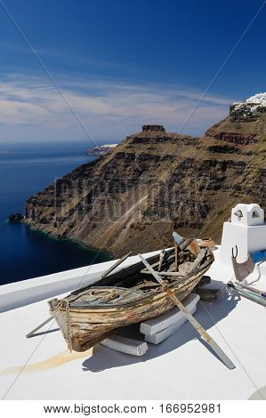 Old wooden fishermans''s boat on roofof house in Firostefani village with typical white architecture, Santorini island, Greece