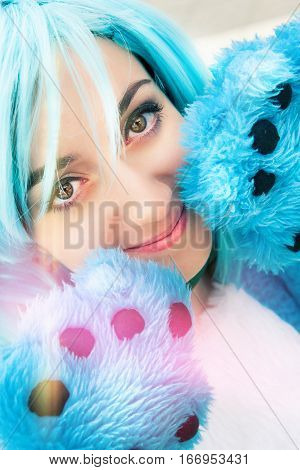 Cosplay girl blue hair costume and paw. Intense eyes. Close portrait of a cosplay face with blue hair. Masquerade costume. Paw with fingers. poster