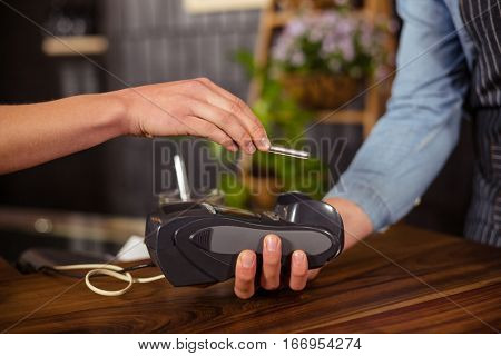 Female customer paying with smartphone at coffee shop