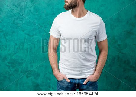 Man in the white t-shirt with space to copy paste standing on the green wall background.