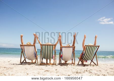 Senior friends sitting in beach chair on the beach