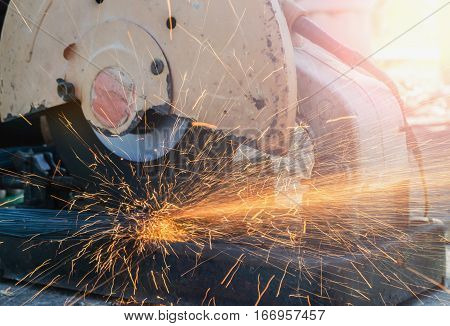 Worker cutting metal with grinder in construction site