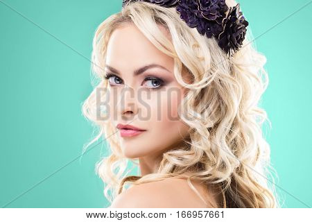 Beauty portrait of attractive blond girl with curly hair and a beautiful headband over cyan green background.