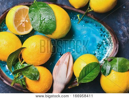 Close-up of freshly picked lemons with leaves in bright blue ceramic plate, top view, copy space, horizontal composition