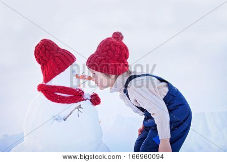 Happy Beautiful Child Building Snowman In Garden, Winter, Nose To Nose With The Snowman