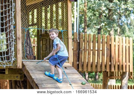 Little Climber Takes The Rope Bridge. Boy Has Fun Time, Kid Climbing On Sunny Warm Summer Day