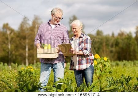 farming, gardening, harvesting, agriculture and people concept - senior couple with box of vegetables and clipboard at farm or garden