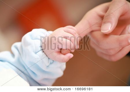 a baby holding his mother's big finger