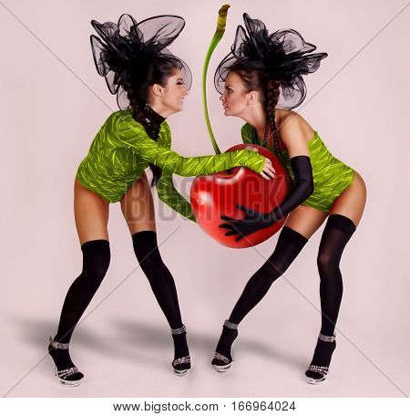 two girls with huge cherry in green costumes
