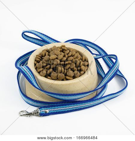 The close up of kibbles (dog food) in brown plastic dog bowl and blue nylon leash.