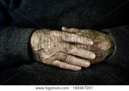 closeup of the wrinkled hands of an old caucasian man, wearing a dark gray sweater
