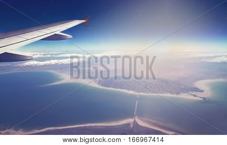 Image Of Plane And Wing With Sea, Mountains, And Coastline. Horizont Line And Sunrise.