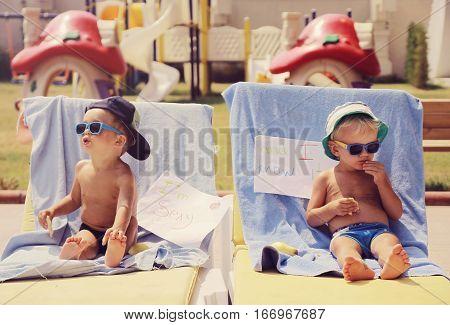 Two cool boys sunbathing near pool .