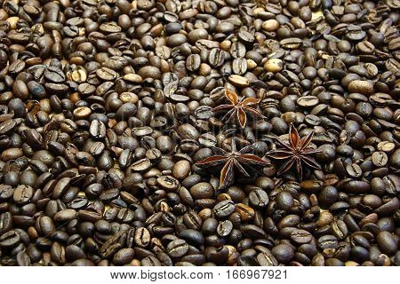 Cooper coffee pot on coffee beans background with several star anise flowers..