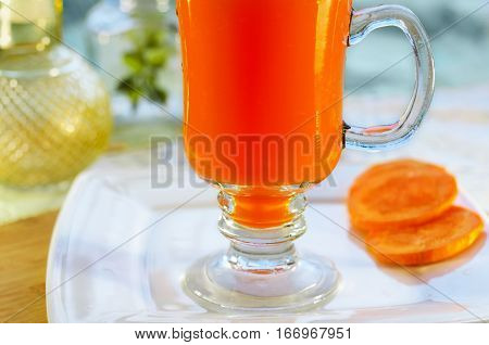 Carrot juice in glass on the stem and a piece of carrot, close-up can not see the edge. Selective focus.