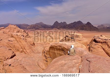 WADI RUM, JORDAN: A Jordanian man overlooking the Wadi Rum desert from the top of a mountain