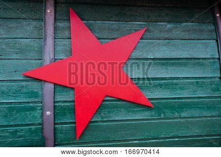 Big red star on green wooden background
