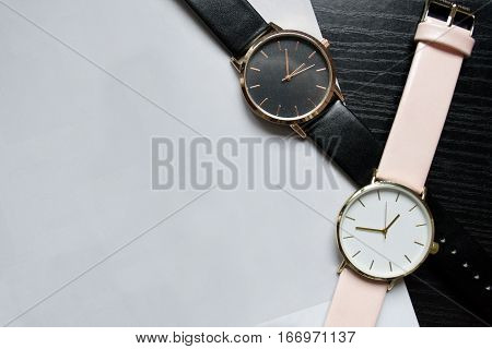 Two watches black and pink color without numbers on a black table. Light paper place for your text. Fashionable concept top view