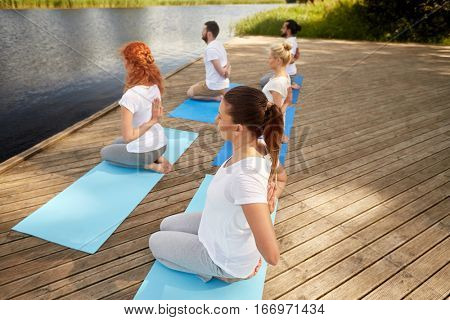 fitness, sport, yoga and healthy lifestyle concept - group of people exercising in reverse prayer pose on river or lake berth