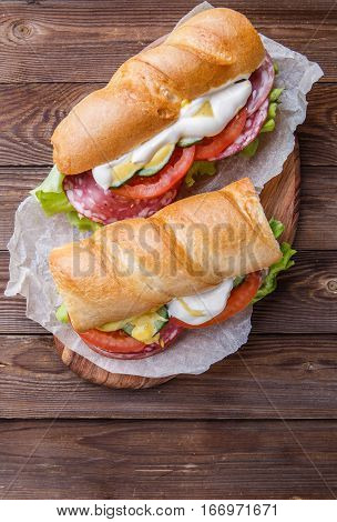 Appetizing sandwich with sausage and vegetables on wooden table