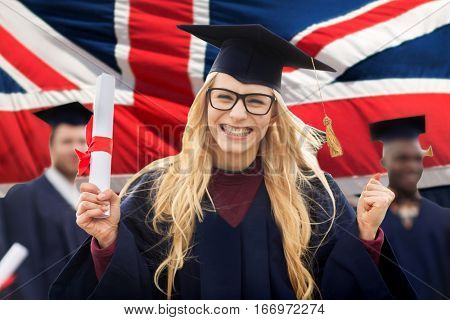 education, gesture and people concept - group of happy international students in mortarboards and bachelor gowns with diplomas celebrating successful graduation over english flag background
