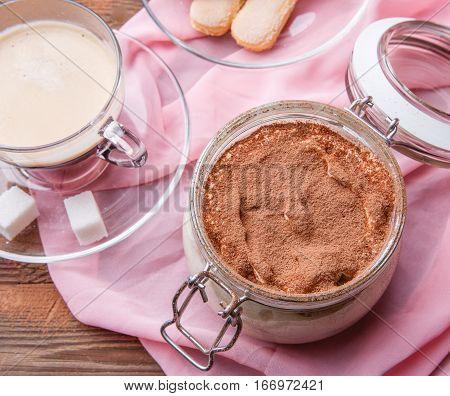 Tiramisu, coffee , savoiardi on pink fabric on brown wooden table