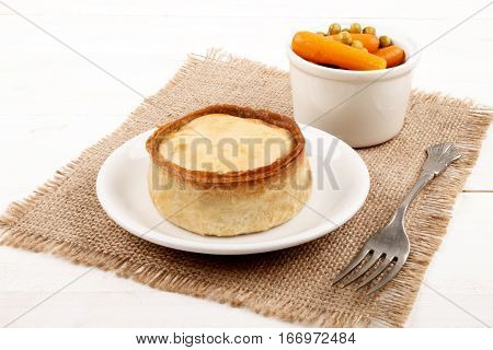 warm scottish pie on a plate and a bowl with pea and carrot