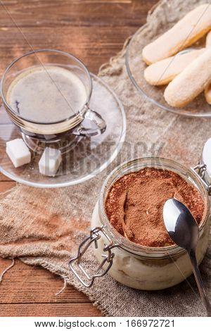 Photo of wooden table with tiramisu, cookies Savoiardi, coffee cup