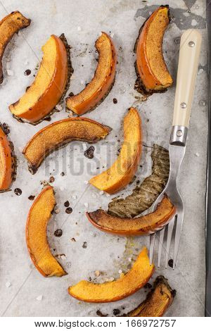 baked pumpkin on white baking paper with fork